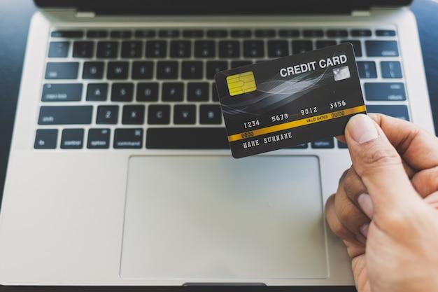 Schließen sie oben von den asiatischen männern, die eine kreditkarte halten und online über laptop kaufen Premium Fotos