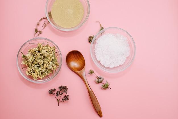 Schließen sie oben von den bestandteilen der ayurvedischen behandlung oder der gesichtsmaske. gelber lehm, gelbwurzpulver und getrocknete kamille, seegrobes salz in den glasschalen auf einer rosa pastellfarboberfläche. flachgelegtes blog Premium Fotos