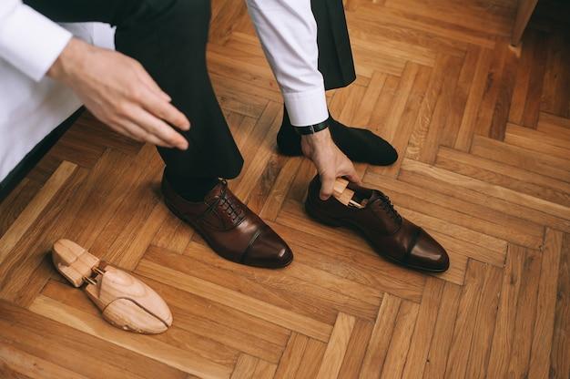 Schließen sie oben von den füßen des bräutigams oder geschäftsmannes, der neue stilvolle schuhe anzieht. herrenhände nehmen holzeinsätze aus schuhen heraus. konzept für menschen, unternehmen, mode und schuhe. Premium Fotos