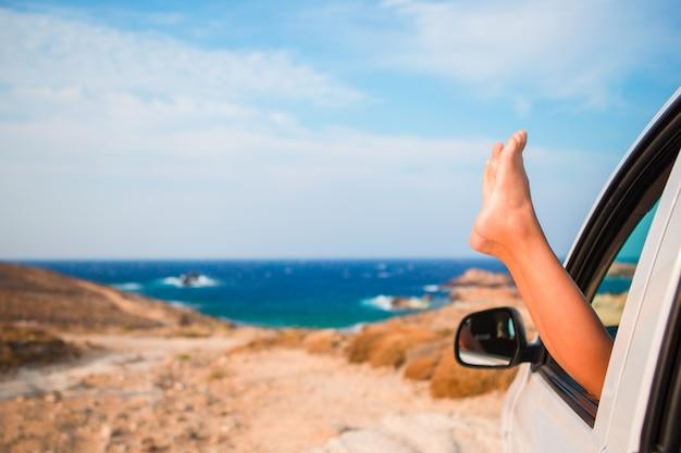 Schließen sie oben von den füßen des kleinen mädchens, die vom autofensterhintergrundmeer darstellen Premium Fotos