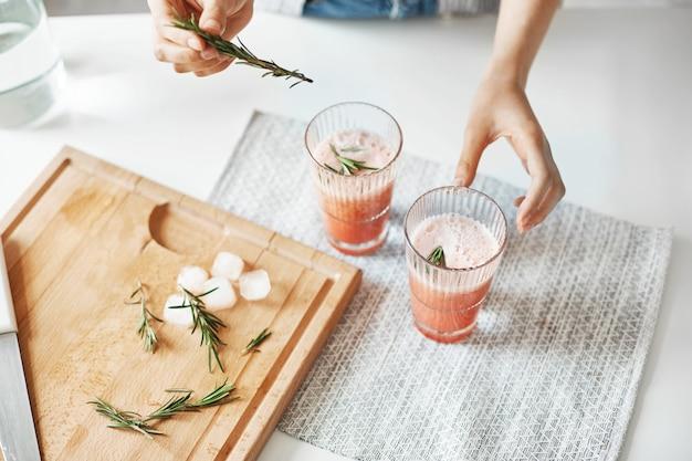 Schließen sie oben von den händen der frau, die gesunden smoothie der grapefruitentgiftung mit rosmarin verzieren. Kostenlose Fotos