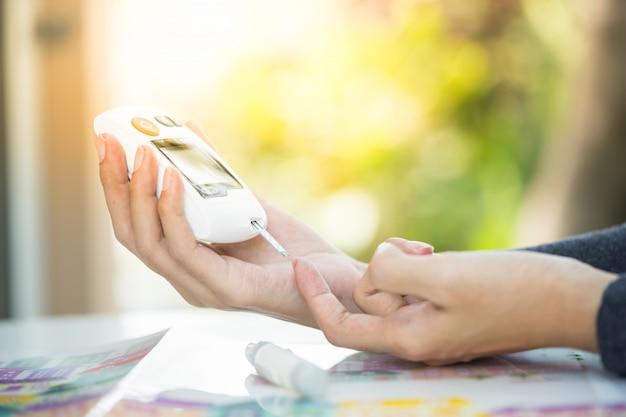 Schließen sie oben von den händen des asiatischen mannes unter verwendung der lanzette auf finger, um blutzuckerspiegel durch glukosemeter zu überprüfen Premium Fotos
