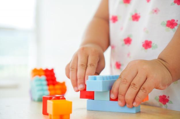 Schließen sie oben von den händen des kindes, die mit bunten verbindungsstückspielwaren am tisch spielen. lernspielzeug für vorschul- und kindergartenkinder. Premium Fotos