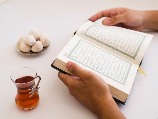 Schließen sie oben von den händen, die quran auf tabelle halten Kostenlose Fotos