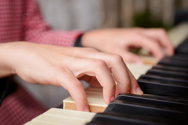 Schließen sie oben von den händen eines kleinen begabten mädchens, das zu hause klavier spielt Premium Fotos