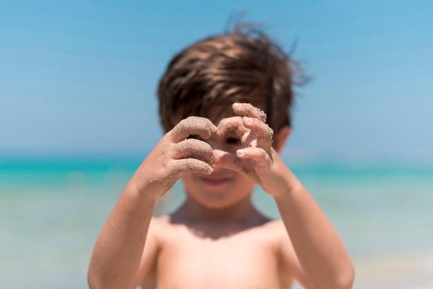 Schließen sie oben von den kinderhänden, die am strand spielen Kostenlose Fotos