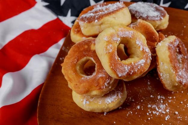 Schließen sie oben von den köstlichen üppigen schaumgummiringen mit spitze über hintergrund der amerikanischen flagge Premium Fotos