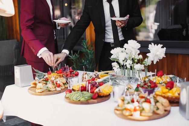 Schließen sie oben von den leuten, welche die früchte im buffet des restaurants sich dienen Kostenlose Fotos