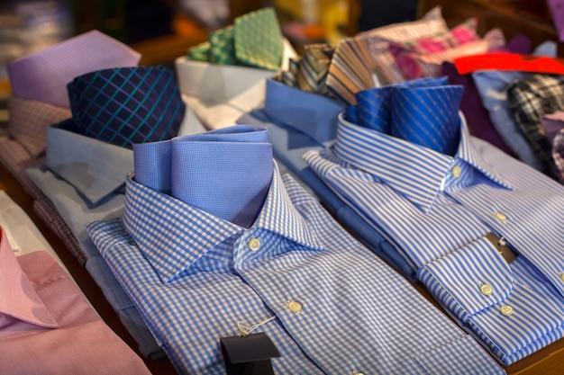 Schließen sie oben von den männlichen hemden, die im kleidergeschäft ausgesetzt sind Premium Fotos