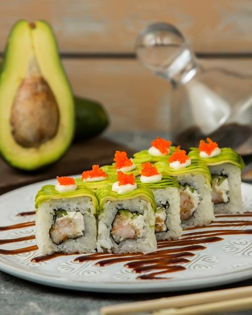 Schließen sie oben von den sushirollen mit garnele, die gurke, die mit avocado bedeckt wird Kostenlose Fotos