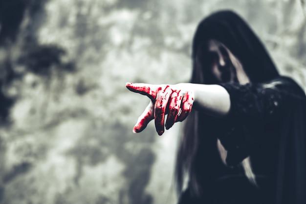 Schließen sie oben von der blutigen geisterhand, die auf die front zeigt. horror und geist konzept Premium Fotos