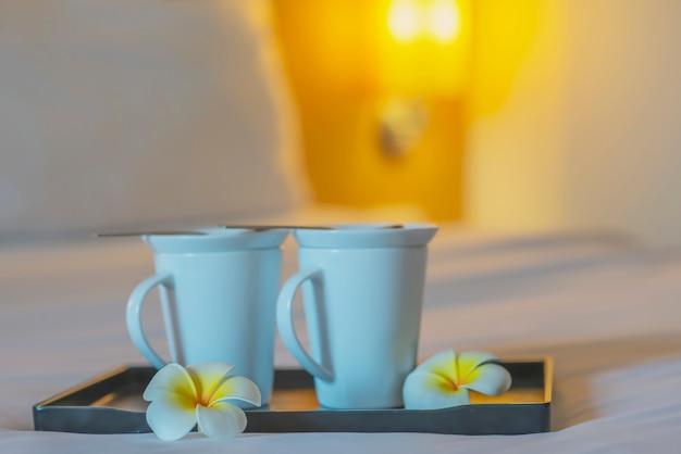 Schließen sie oben von der doppelwillkommenskaffeetasse auf weißem bett im hotelzimmer - hotelbrunnengastfreundschafts-urlaubsreisekonzept Kostenlose Fotos