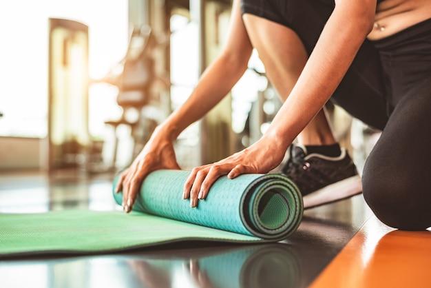 Schließen sie oben von der faltenden yogamatratze der sportlichen frau im sporteignungsturnhallentrainingszentrumhintergrund. Premium Fotos