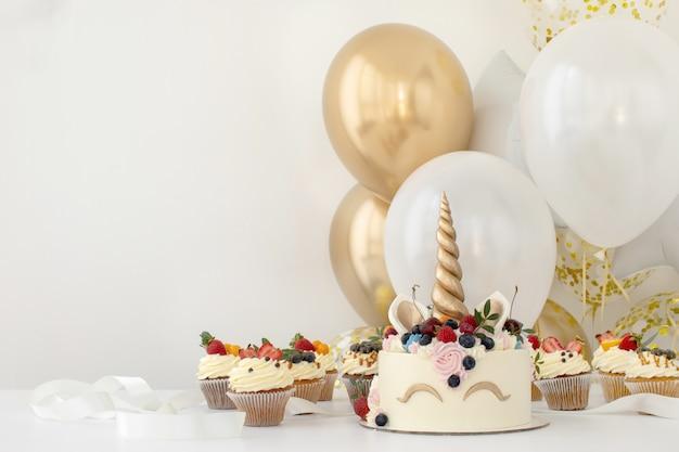 Schließen sie oben von der geburtstagsfeiertabelle des kleinen mädchens mit einhornkuchen Premium Fotos
