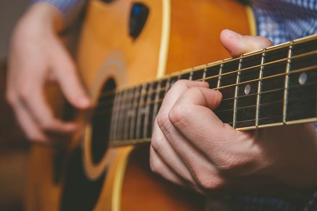 Schließen sie oben von der gitarristhand, die gitarre spielt Premium Fotos