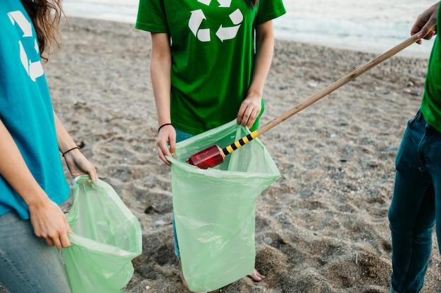 Schließen sie oben von der gruppe freiwilligen, die abfall am strand sammeln Kostenlose Fotos
