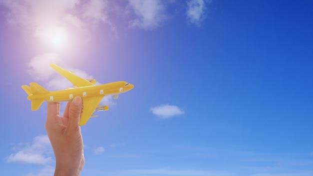 Schließen sie oben von der hand der frau, die spielzeugflugzeug auf hintergrund des blauen himmels mit sonnenschein hält. Premium Fotos