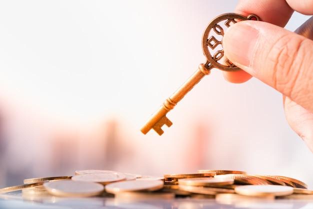 Schließen sie oben von der hand des mannes, die schlüssel auf stapel der münze mit stadtbild als hintergründen hält. Premium Fotos