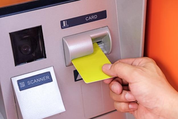 Schließen sie oben von der hand des mannes einstecken atm-karte in geldautomaten Premium Fotos