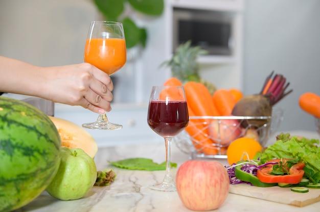 Schließen sie oben von der hand, die ein glas des gesunden safts hält, während gemüse und entsafter auf dem tisch in der küche, gesundheitskonzept Premium Fotos