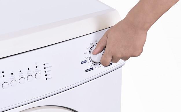 Schließen sie oben von der hand, die waschmaschinenprogramm justiert Premium Fotos