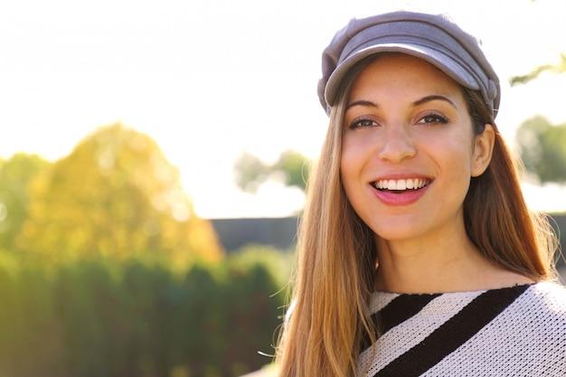 Schließen sie oben von der jungen modefrau mit hut im park auf herbstsaison. kamera betrachten. Premium Fotos