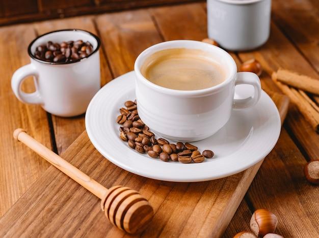 Schließen sie oben von der kaffeetasse, die mit kaffeebohnen verziert wird, die auf hölzernem servierbrett platziert werden Kostenlose Fotos