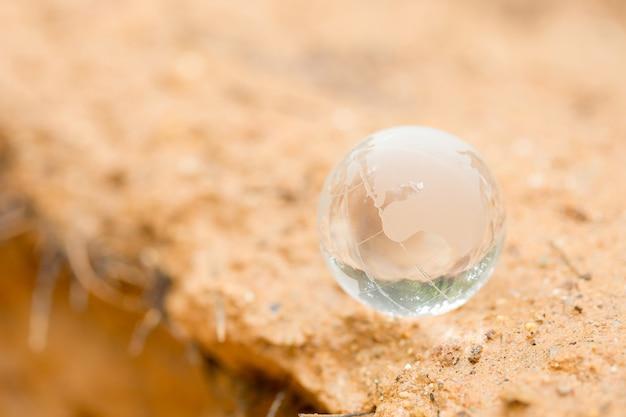 Schließen sie oben von der kristallkugel, die auf schlamm stillsteht. Kostenlose Fotos