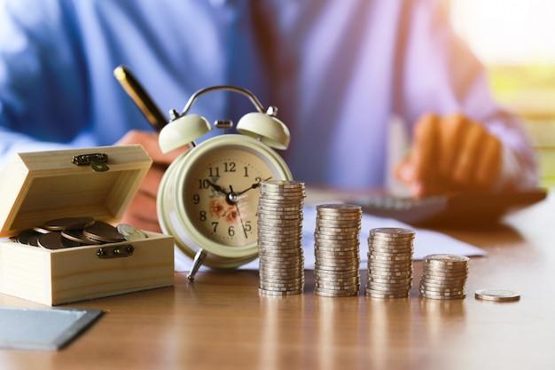 Schließen sie oben, von der leutehand, die die münzen auf den tisch in sein büro setzt. Premium Fotos