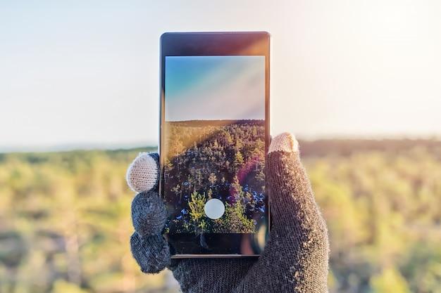 Schließen sie oben von der männlichen hand, die intelligentes telefon hält und foto macht Premium Fotos