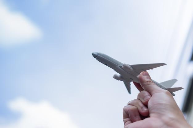 Schließen sie oben von der mannhand, die flugzeugspielzeug hält und zum himmel anheben Premium Fotos