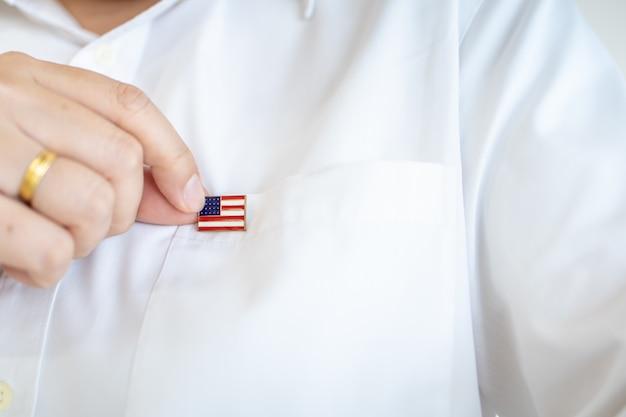 Schließen sie oben von der mannhand, die nationsflaggenstift des vereinigten staaten von amerika von der weißen hemdflagge hält. Premium Fotos