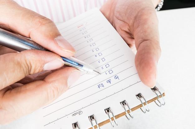 Schließen sie oben von der mannhand, die notizbuch mit der handschrift hält und schreibt, um liste zu tun. Premium Fotos