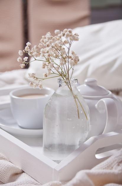 Schließen sie oben von der tasse tee, von der milch, von der teekanne und vom blumenstrauß von weißen blumen auf dem weißen behälter. Premium Fotos
