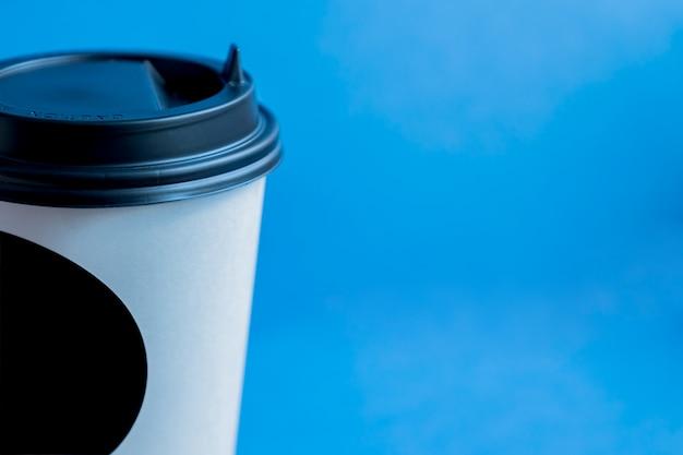 Schließen sie oben von der weißbuchkraftpapier-wegwerfschale für kaffee mit schwarzem plastikdeckel auf blau mit kopienraum Premium Fotos