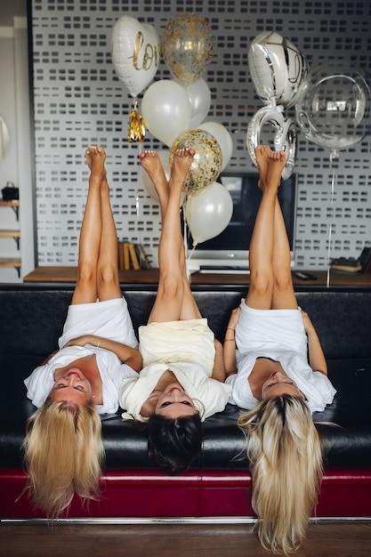 Schließen sie oben von drei paaren weiblichen beinen mit pediküre in einer luft. Premium Fotos