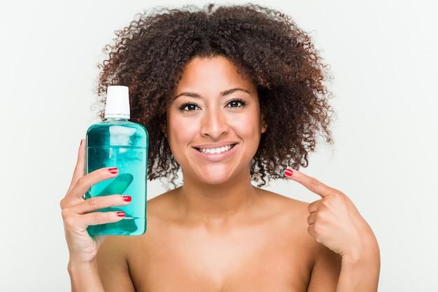 Schließen sie oben von einer jungen afroamerikanerfrau, die ein mundwasser hält Premium Fotos