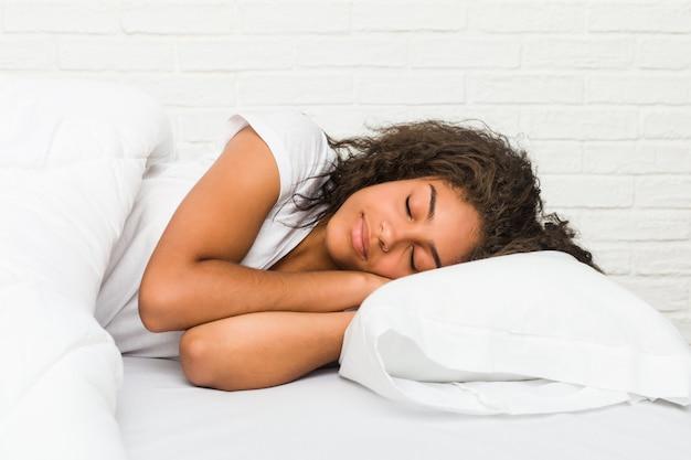 Schließen sie oben von einer jungen afroamerikanermüden frau, die auf dem bett schläft Premium Fotos
