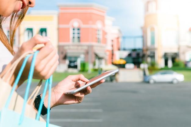 Schließen sie oben von einer jungen frau halten einkaufstaschen in ihrer hand und plaudern an ihrem telefon nach dem einkauf Kostenlose Fotos
