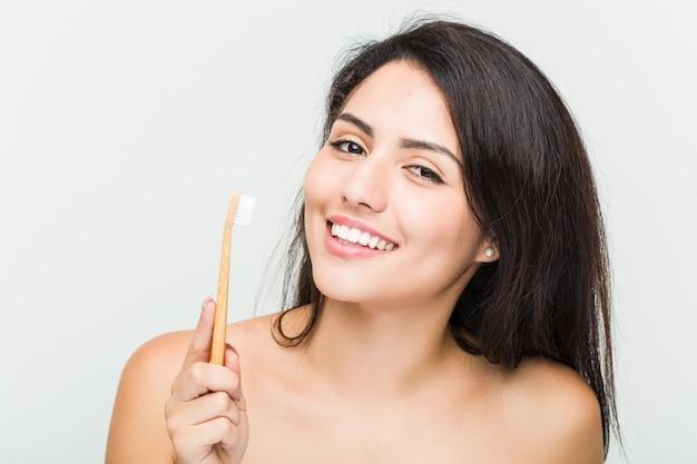 Schließen sie oben von einer jungen schönen und natürlichen hispanischen frau, die eine zahnbürste hält Premium Fotos