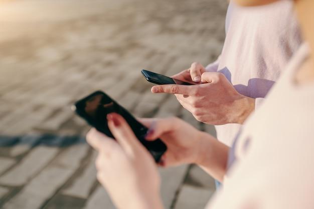 Schließen sie oben von mann und frau, die smartphones verwenden, während sie nebeneinander im freien stehen Premium Fotos