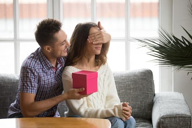 Schließende augen des liebevollen ehemanns der frau, die romantisches überraschungsgeschenk darstellt Kostenlose Fotos