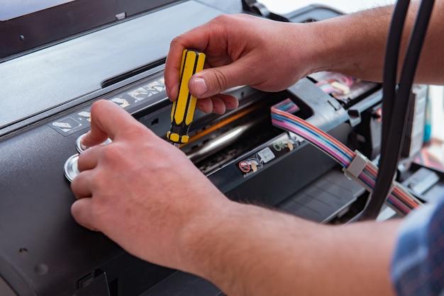 Schlosser, der defekten farbdrucker repariert Premium Fotos