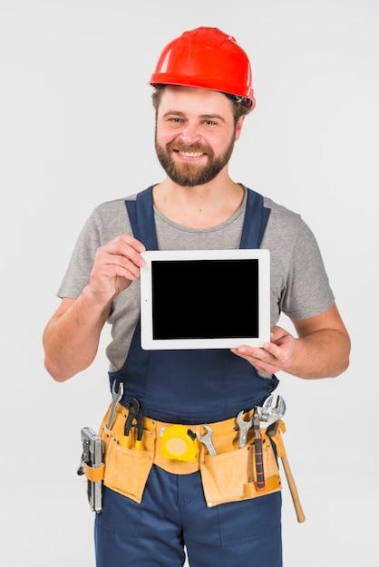 Schlosser in der gesamtheit, die tablette mit leerem bildschirm hält Kostenlose Fotos