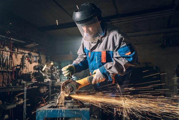 Schlosser in spezialkleidung und schutzbrille arbeitet in der produktion. metallbearbeitung mit winkelschleifer. funken in der metallbearbeitung. Premium Fotos