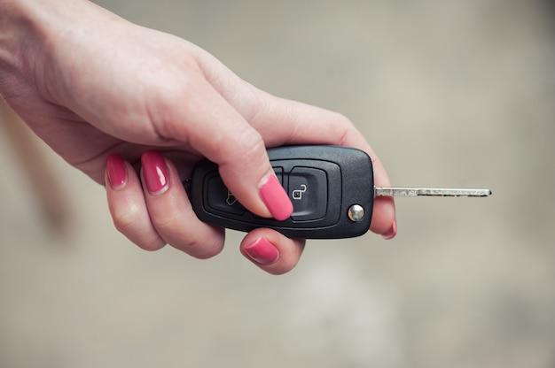 Schlüssel aus dem auto in weiblicher hand. autoverkäufer. öffnen und signalisieren. autoverkauf und gegenwart Premium Fotos
