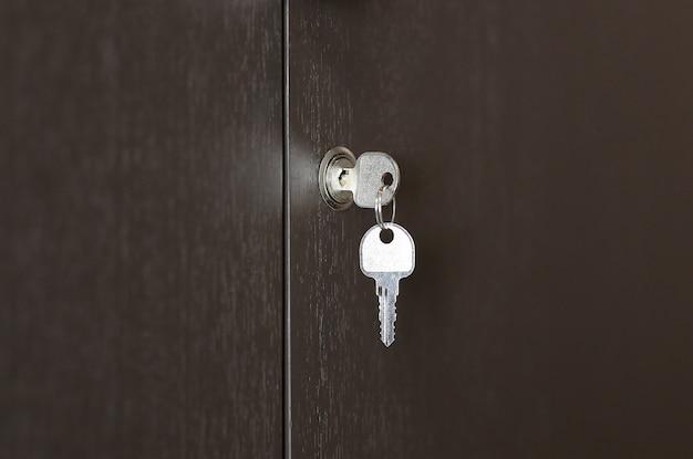 Schlüssel im schlüsselloch auf holzschrank, schlüssel im schloss. Premium Fotos