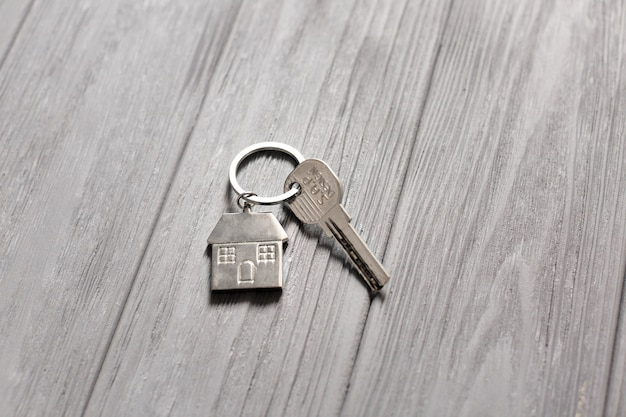 Schlüssel mit kleinem haus auf holztisch Kostenlose Fotos