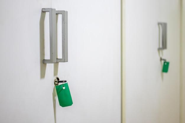 Schlüssel und grünes etikett auf den schränken Premium Fotos