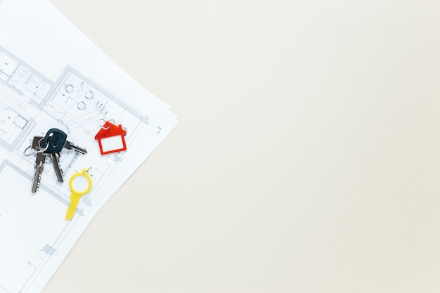 Schlüssel und haus formen keychain auf plan über weißem hintergrund Kostenlose Fotos